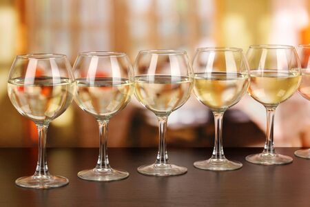 wine tasting: White wine in glass on room background