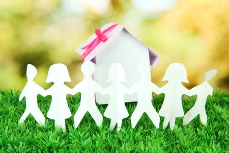 Paper people on green grass on bright background Stock Photo - 16805508