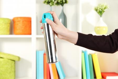 Sprayed air freshener in hand on white shelves background Stock Photo - 16805022