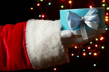 Santa Claus hand holding gift box on bright background Stock Photo - 16864894
