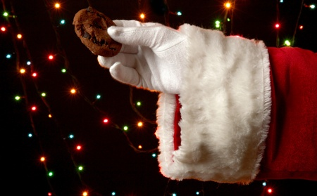 hots: Santa Claus hand holding chocolate cookie on bright background Stock Photo
