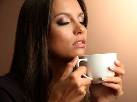 drinking tea: beautiful young woman with cup of coffee, on brown background