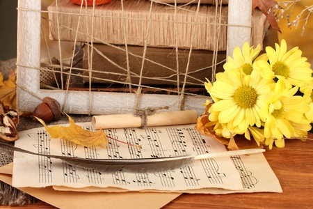 Autumnal composition with notes sheet, flowers and leaves on bright background photo