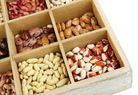 Diverse beans in wooden box sections isolated on white Stock Photo - 16865334