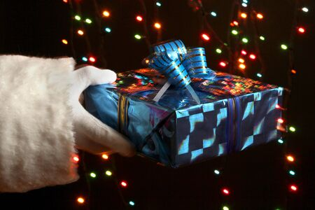 Santa Claus hand holding gift box on bright background Stock Photo - 16865336