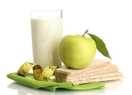 Glass of kefir, green apples, crispbreads and measuring tape isolated on white photo