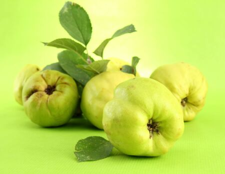 sweet quinces with leaves, on green background photo