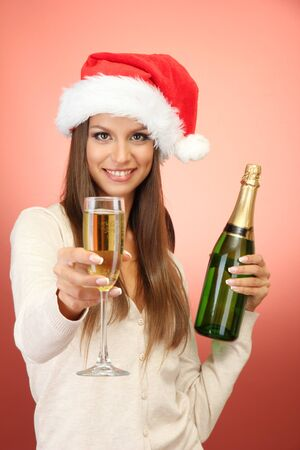 beautiful young woman with bottle and glass of champagne, on red background Stock Photo - 17132877