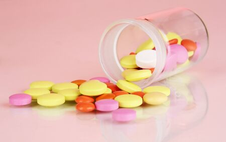 Pills in receptacle on red background Stock Photo - 16865121