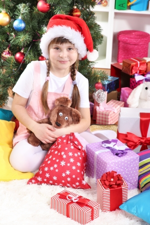 festively: Little girl in Santa hat near the Christmas tree in festively decorated room Stock Photo