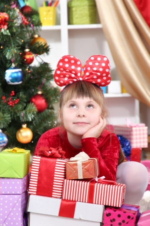 Dreaming little girl in red dress surrounded by gifts in festively decorated room photo