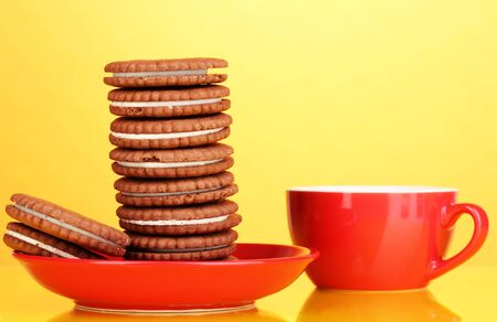 Chocolate cookies with creamy layer on red plate yellow background photo