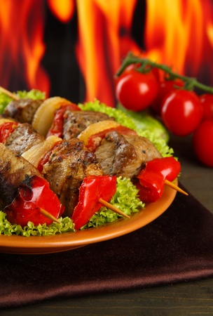 tasty grilled meat and vegetables on plate, on fire background Stock Photo - 16865290