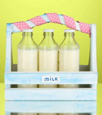 Milk in bottles in wooden box on green background photo