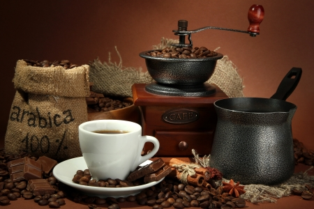 cup of coffee, grinder, turk and coffee beans on brown background Stock Photo - 16949203