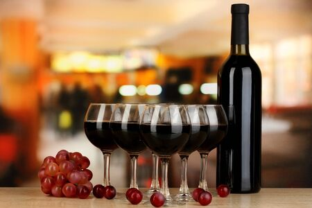 red taste: Red wine in glass and bottle on room background