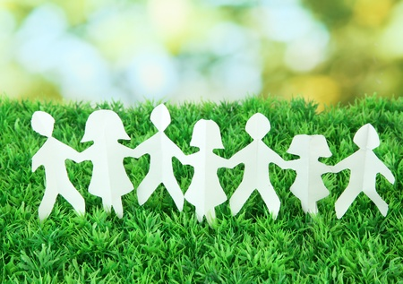 linked together: Paper people on green grass on bright background