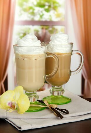Fragrant coffee latte in glasses cups with vanilla pods, on table in cafe photo