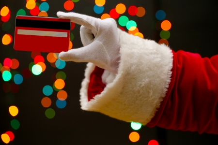 Santa Claus hand holding credit card, on garland background  Stock Photo - 16949008