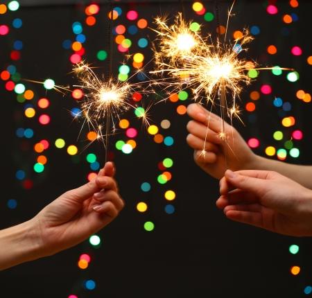 beautiful sparklers in woman hands on garland background  photo