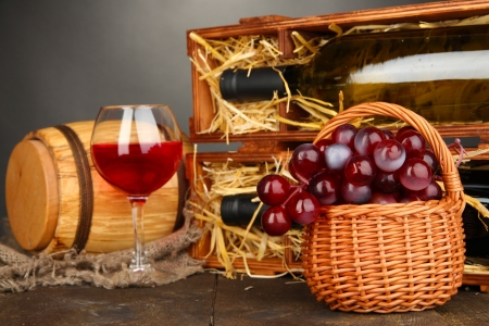 Wooden case with wine bottles, barrel, wineglass and grape on wooden table on grey background Stock Photo - 16949206
