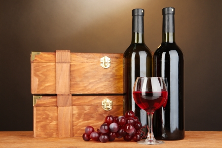 Wooden cases with wine bottles on wooden table on brown background photo
