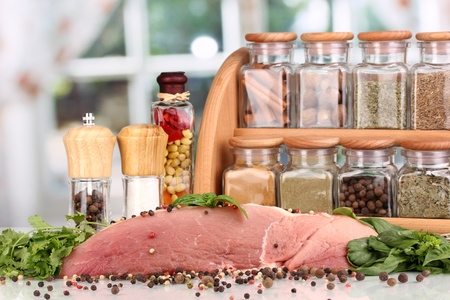 microelements: A large piece of pork marinated with herbs and spices on white table on window background Stock Photo