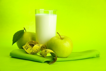 Glass of kefir, apples and measuring tape, on green background photo