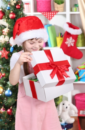 festively: A little girl opens a gift in festively decorated room Stock Photo