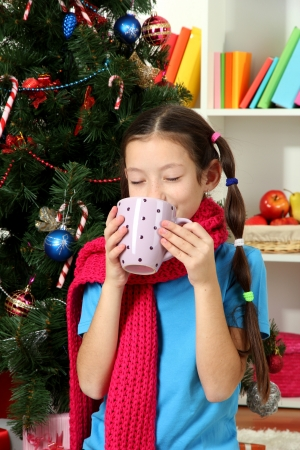 Little girl with pink scarf and cup of hot drink  sitting near christmas tree photo
