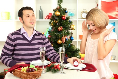 Young man makes proposal to marry girl at table near Christmas tree photo