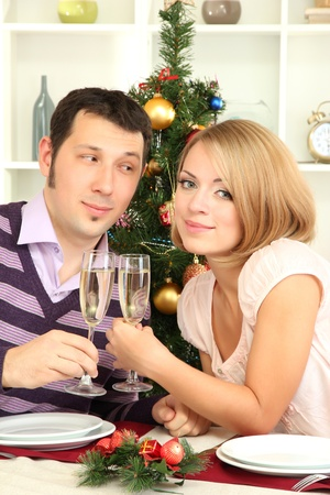 Young happy couple holding glasses with champagne at table near Christmas tree photo