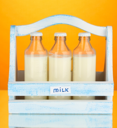 Milk in bottles in wooden box on orange background photo