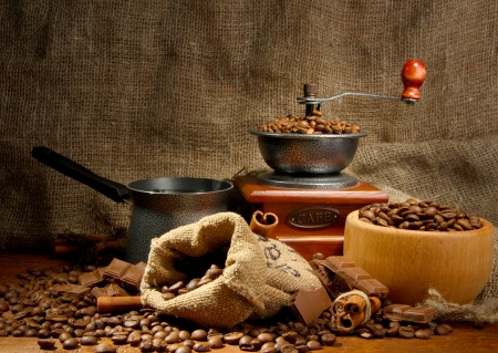 Coffee grinder, turk and cup of coffee on burlap background photo