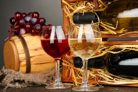 Wooden case with wine bottles, barrel, wineglass and grape on wooden table on grey background Stock Photo - 16914444