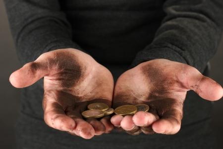 manos sucias: hombre desamparado con algunas monedas, primer plano Foto de archivo