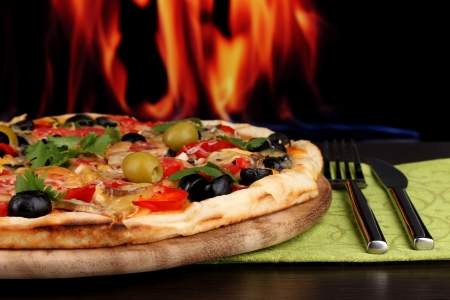 Delicious pizza close-up on wooden table on fire background Stock Photo - 16938800