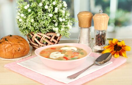 Fragrant soup in pink plate on table on window background close-up photo
