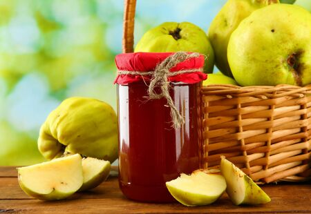 quinces: jar of jam and quinces with leaves in basket, on green background