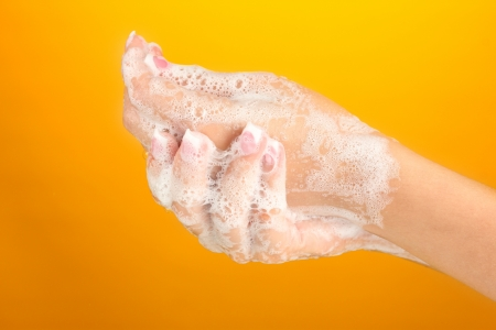 Womans hands in soapsuds, on orange background close-up Stock Photo