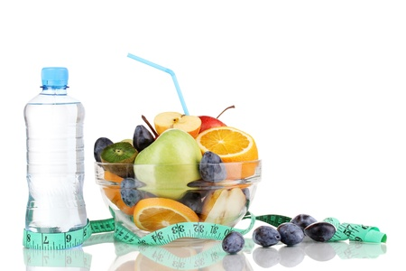 Glass bowl with fruit for diet, measuring tape and water bottle isolated on white photo