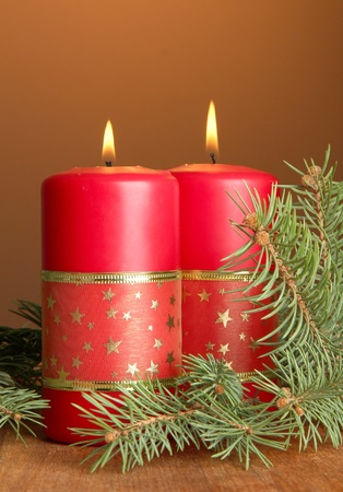 Two candles and christmas tree, on brown background photo