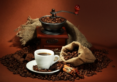cup: cup of coffee, grinder, turk and coffee beans on brown background