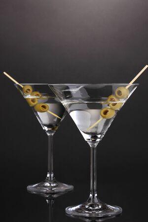 Martini glasses and olives on grey background photo