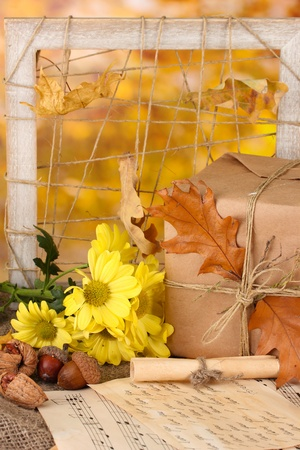 Autumnal composition with gift,flowers and leaves on bright background photo