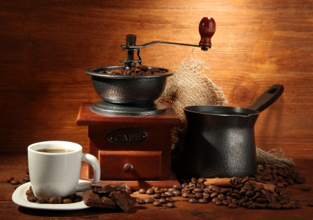 Coffee grinder, turk and cup of coffee on brown wooden background Stock Photo - 16980158
