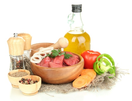 microelements: Raw beef meat in bowl with herbs, spices and cooking oil isolated on white