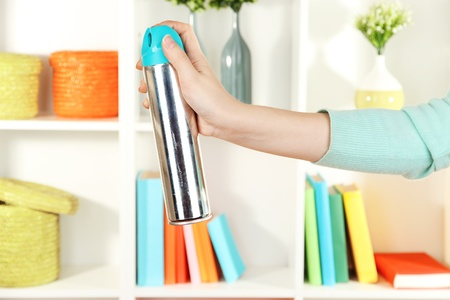 Sprayed air freshener in hand on white shelves background Stock Photo - 16980287