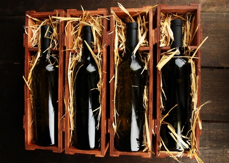 Wooden case with wine bottles on wooden table Stock Photo - 16980119