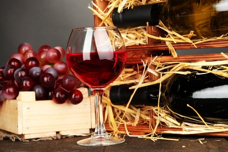 Wooden case with wine bottles, wineglass and grape on wooden table on grey background photo